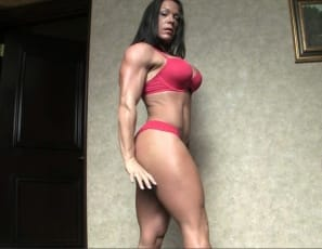 Ripped female bodybuilder Bella is posing, showing off her big, vascular biceps
